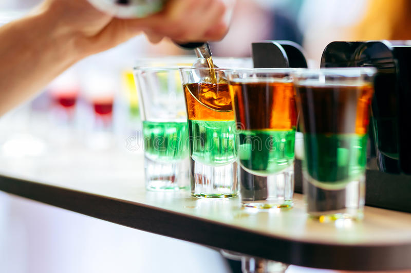 Bartender pouring alcoholic cocktail in shot glasses on bar stock photography