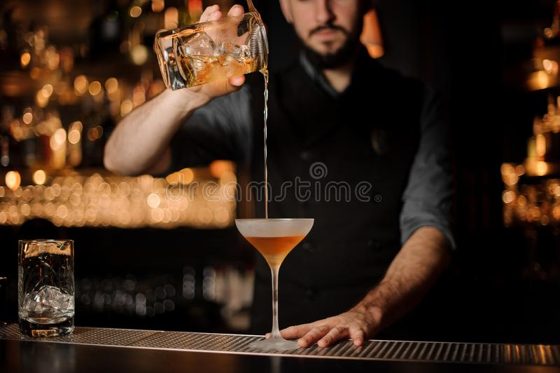 Bartender pouring an alcoholic drink from the measuring cup through the strainer to the matte cocktail glass stock photos