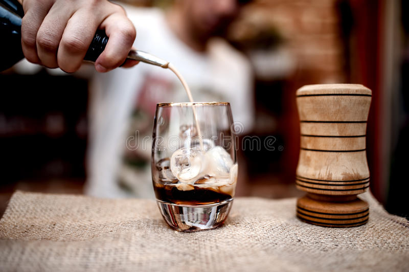 Bartender pouring alcoholic liquor in small glass on the counter royalty free stock photos