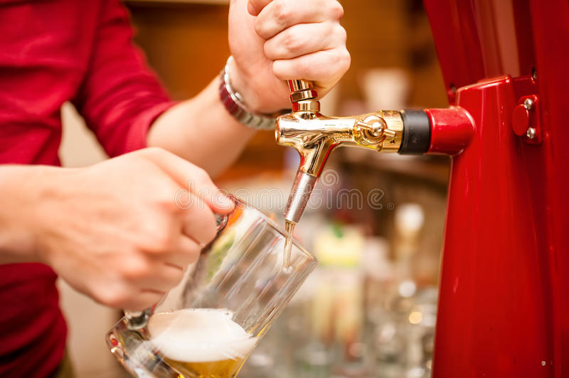 Bartender pouring beer draft in pub, bar. Or nightclub royalty free stock photography
