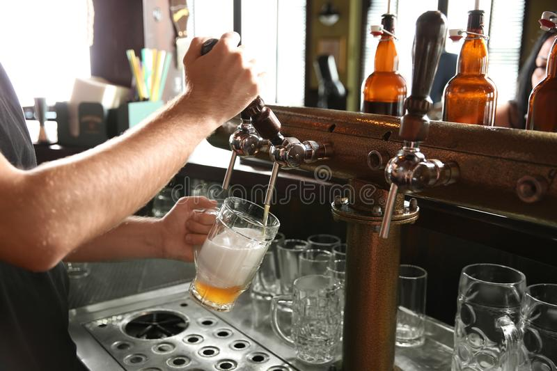 Bartender pouring beer from tap into glass in bar,. Closeup royalty free stock photo