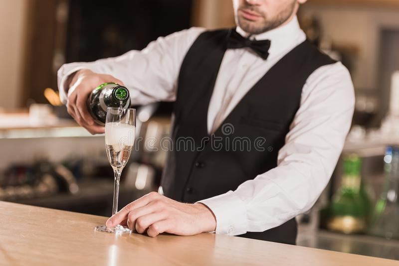Bartender pouring champagne into glass royalty free stock photography