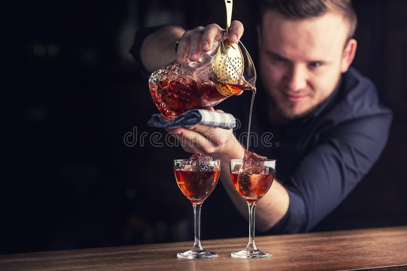 Bartender pouring cocktail alcoholic drink Manhattan. royalty free stock photography