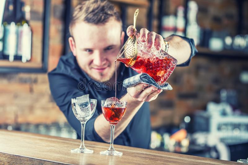 Bartender pouring cocktail alcoholic drink Manhattan. royalty free stock photos