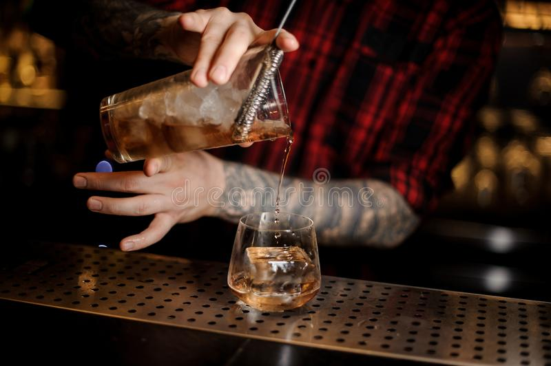 Bartender pouring fresh drink into a whiskey dof glass. Bartender pouring fresh and cold drink into a whiskey dof glass on the bar counter stock images