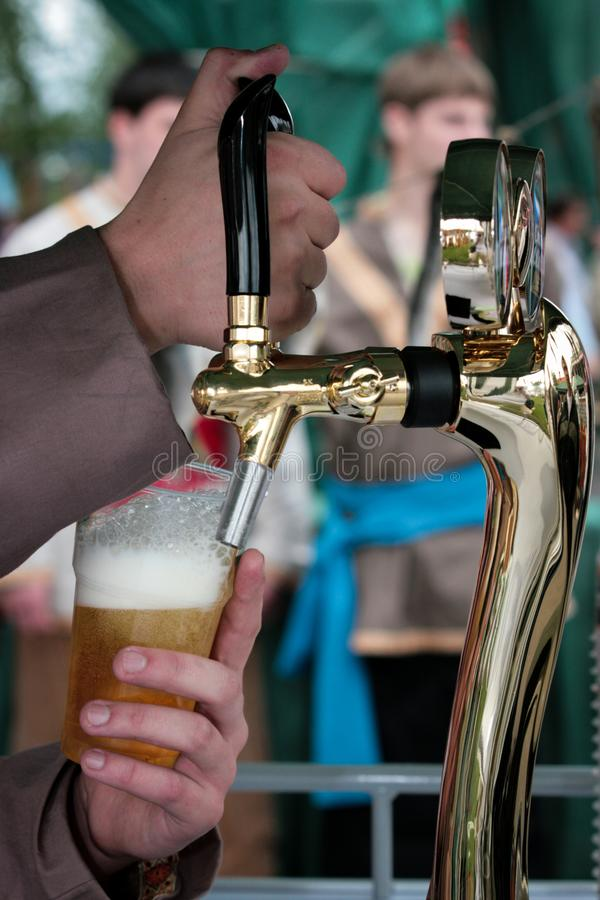 Bartender pouring a glass of fresh beer royalty free stock image