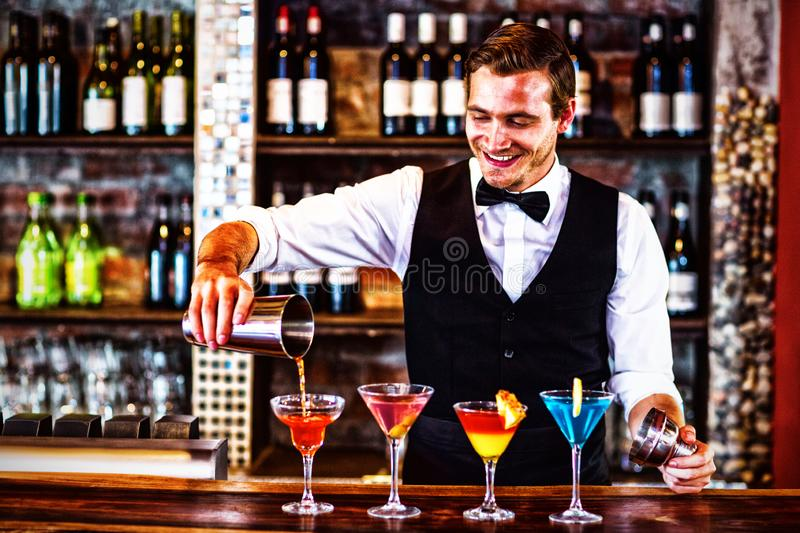 Bartender pouring a orange martini drink in the glass. At bar stock photos