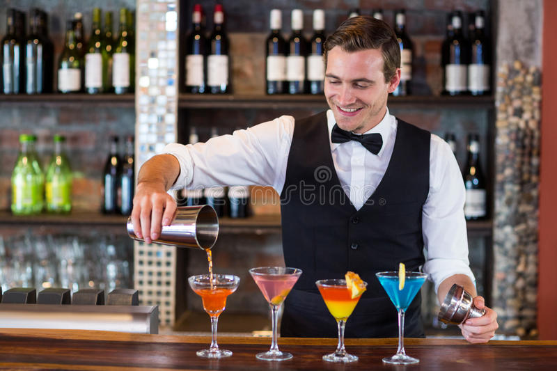 Bartender pouring a orange martini drink in the glass. At bar royalty free stock image