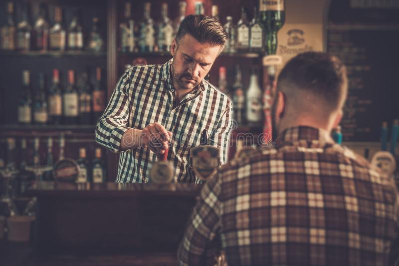 Bartender pouring a pint of beer to customer in a pub. Handsome bartender pouring a pint of beer to customer in a pub stock photo