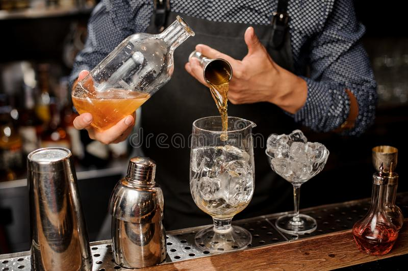 Bartender pouring a portion of syrup into the large cocktail glass. With ice cubes on the bar counter royalty free stock photography