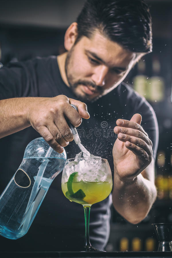 Bartender is pouring soda water. He is preparing a mango cocktail royalty free stock photography