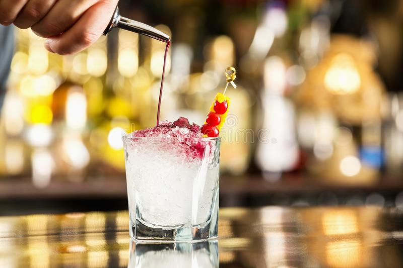 Bartender is pouring syrup to a glass with cocktail at bar royalty free stock photography