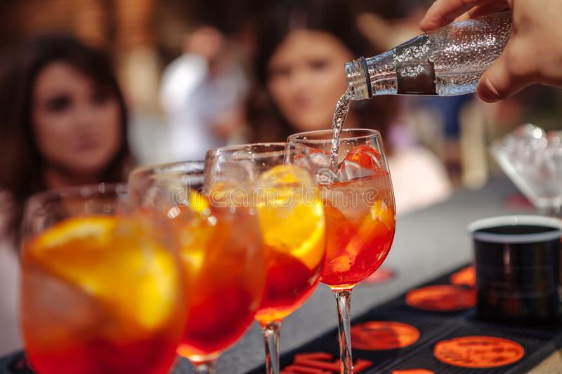 Bartender pours water into a glass with a cocktail. Barman making a cocktail. Close-up. Girls watch as a bartender making a cocktail royalty free stock image
