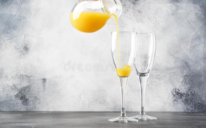 Bartender preparing alcohol cocktail mimosa with orange juice and cold dry champagne or sparkling wine in glasses, gray bar. Counter background copy space royalty free stock photo