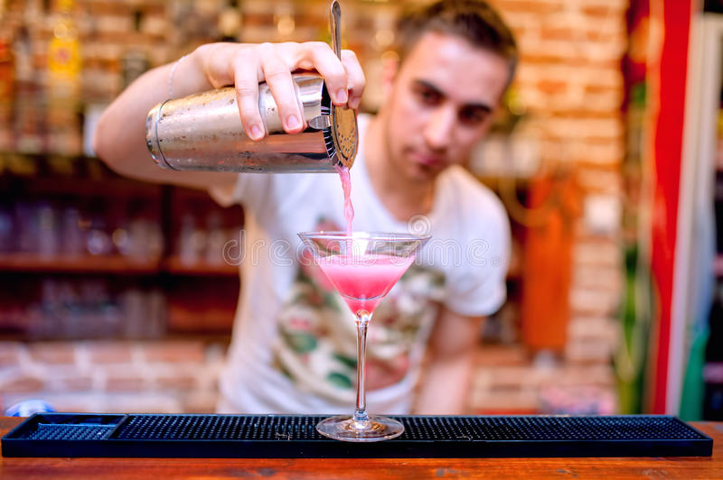 Bartender preparing and pouring cosmopolitan alcoh stock images