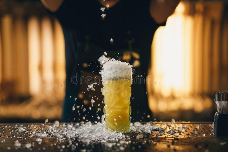 Bartender` s räcker att strila fruktsaften in i coctailexponeringsglaset som fylls med alkoholdrycken på den mörka bakgrunden royaltyfria foton