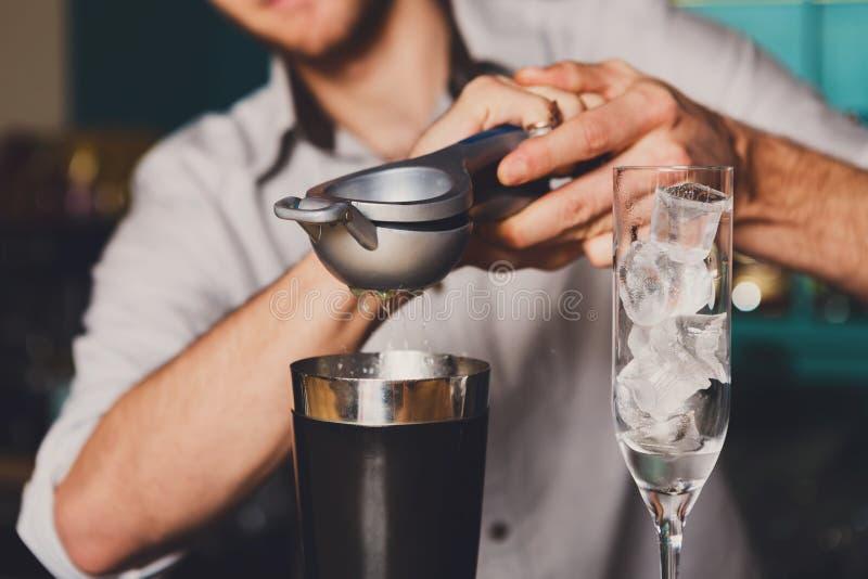Bartender` s räcker danandecoctailen med limefrukt arkivfoto
