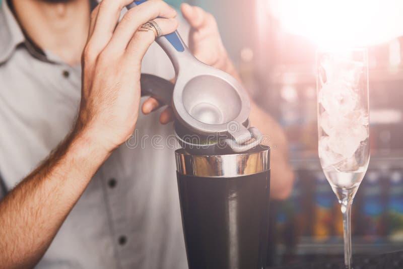 Bartender` s räcker danandecoctailen med limefrukt arkivbild