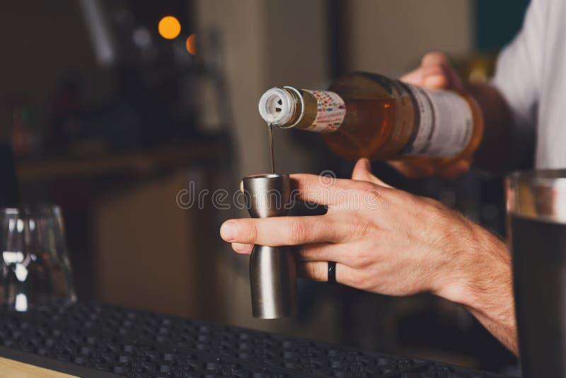 Bartender` s räcker danandeskottcoctailen royaltyfria foton
