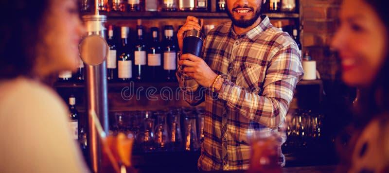 Bartender som blandar en coctaildrink i shaker royaltyfria foton