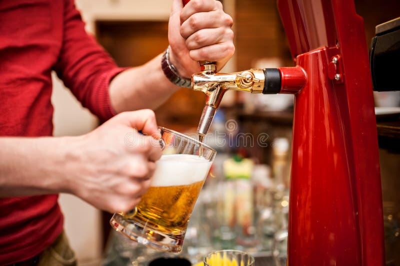 Bartender som bryggar ett utkast, ofiltrerat öl på baren royaltyfri foto