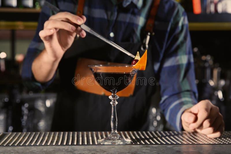 Bartender som dekorerar den alkoholiserade coctailen på räknaren i nattklubb arkivfoton