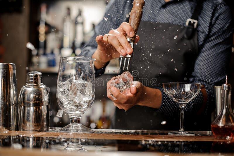 Bartender som delar ett stycke av is på en stångräknare royaltyfria foton