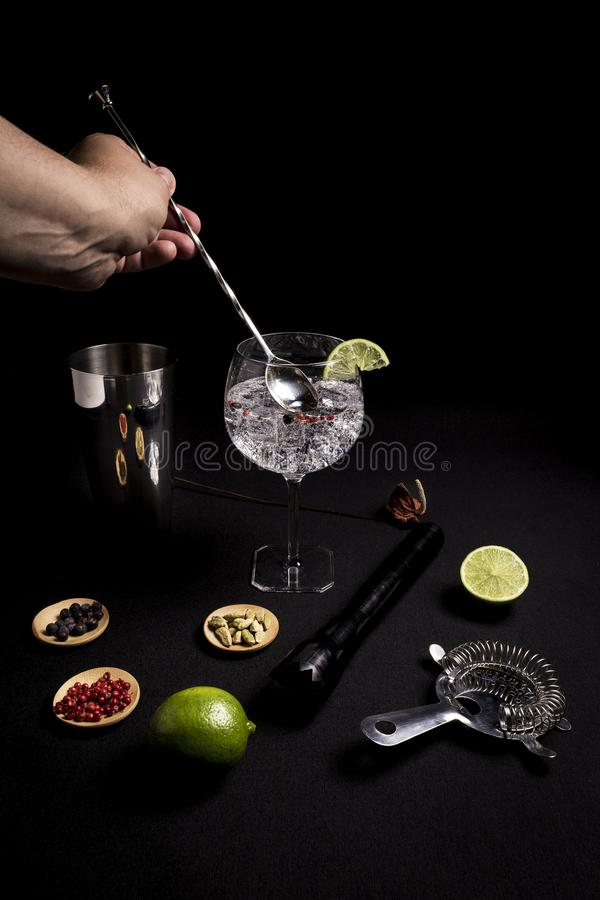Bartender som förbereder en gin- och uppiggningsmedelcoctail på en svart bakgrund bredvid hans ingredienser arkivbilder