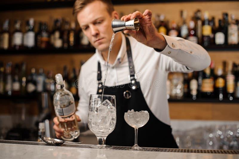 Bartender som häller en del av vodka in i ett exponeringsglas arkivbild