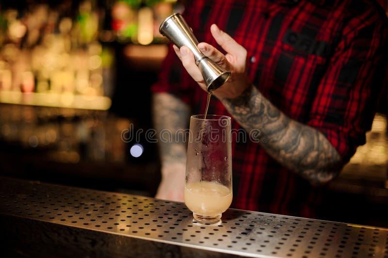 Bartender som häller en Trinidad Swizzle coctail från stålgrejen till exponeringsglaset royaltyfri fotografi