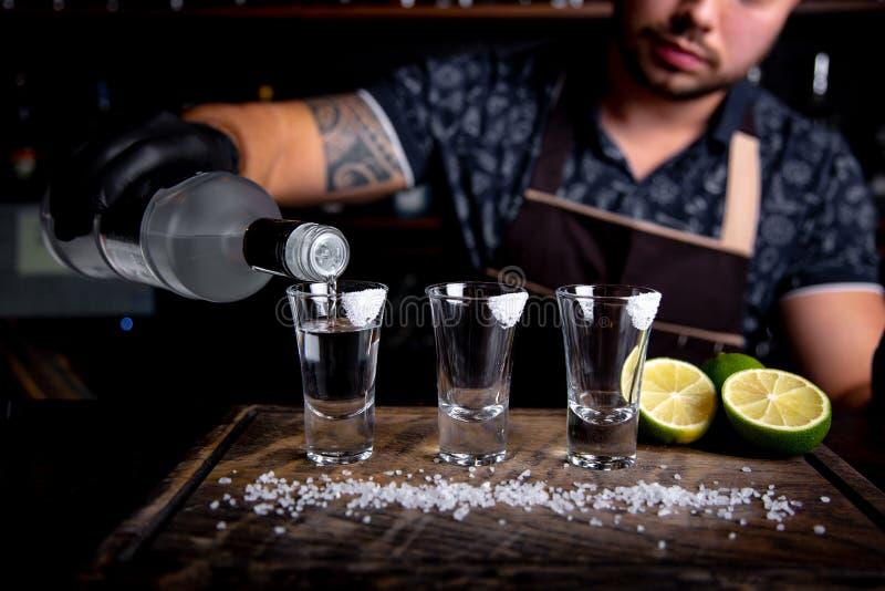Bartender som häller hård ande in i små exponeringsglas liksom alkoholiserade skott av tequilaen eller den starka drinken arkivfoto