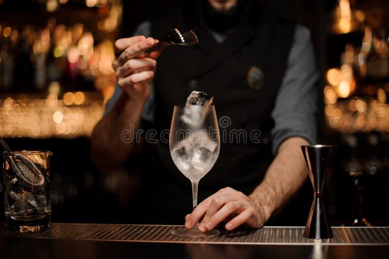 Bartender som kastar till kub för is för coctailexponeringsglas ett en stor royaltyfria bilder