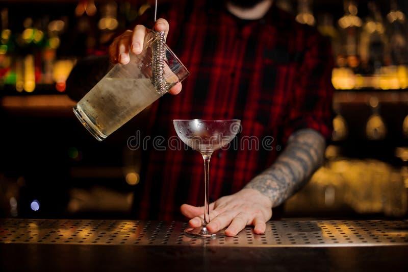 Bartender som pourring en achoholic drink för glimt från mäta arkivfoto