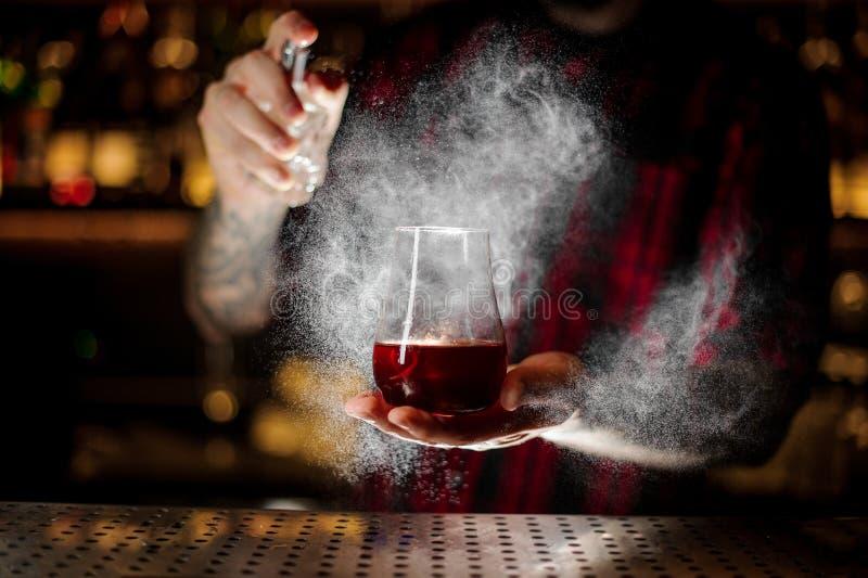 Bartender som strilar bitterhet in i exponeringsglaset med den röda söta coctailen royaltyfria bilder