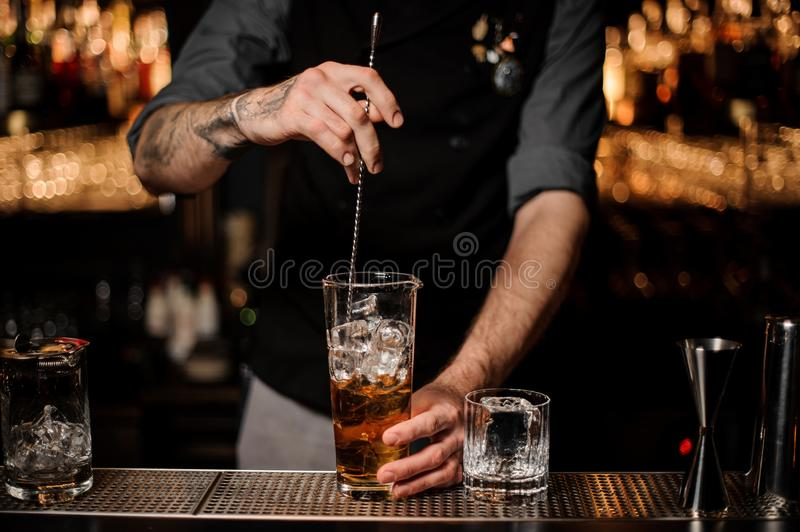 Bartender stirring many ice cubes in the tall glass with a brown cocktail with a spoon. On the bar counter on the blurred background stock photography