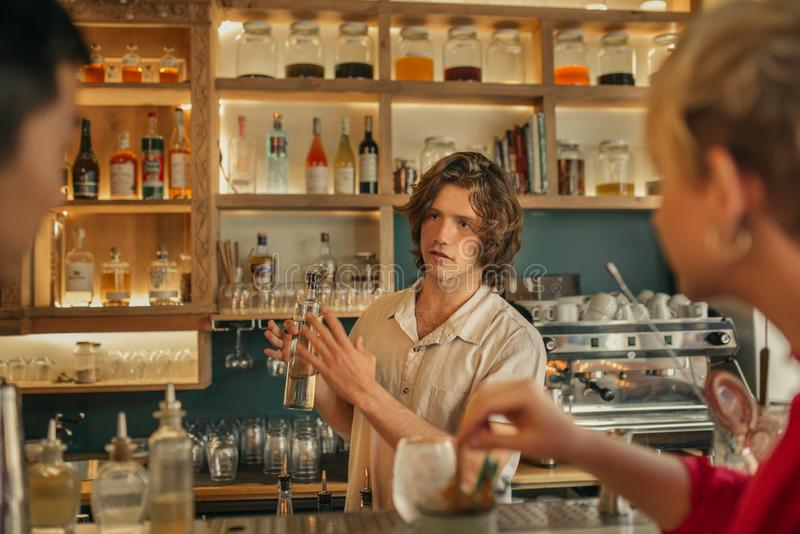 Bartender taking drink orders from customers in a trendy bar. Young male bartender holding a bottle while standing behind the counter of a trendy bar taking stock photography