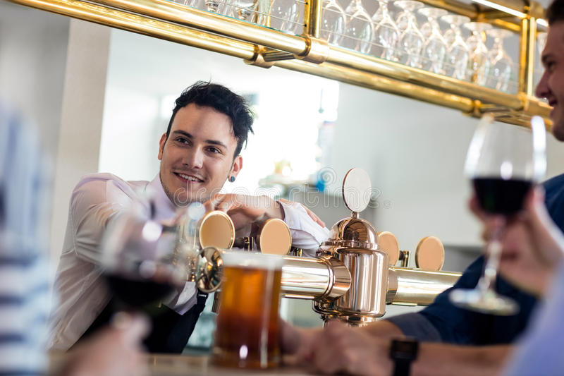 Bartender talking with customers counter royalty free stock photos