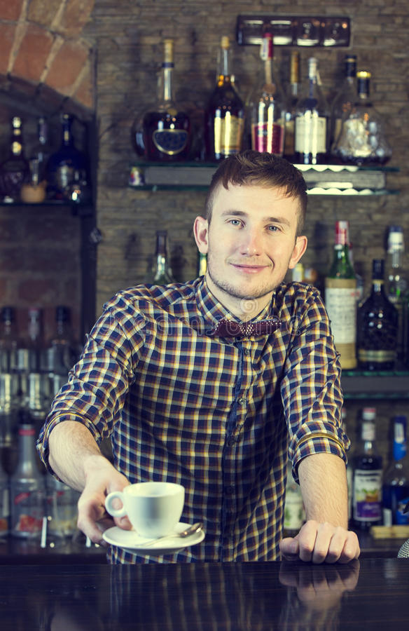 Bartender. Young man working as a bartender in a nightclub bar stock image