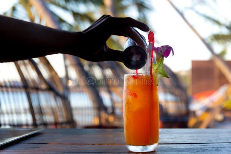 Bartenderdanandecoctail på stången på stranden och tillfogaflytande i ett exponeringsglas arkivbild