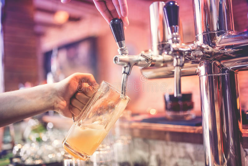 Bartenderhand på ölklappet som häller ett utkastlageröl på restaurangen, baren eller bistroer arkivbild