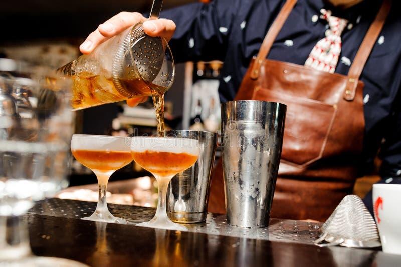 Bartendern avslutar förberedelsen av två alkoholiserade coctailar genom att använda stångutrustning arkivbild
