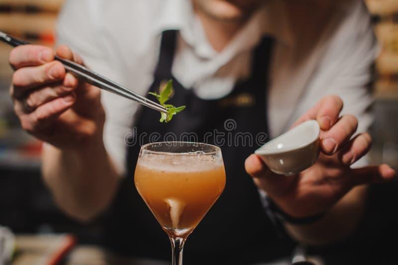 Bartendern dekorerar coctailen med raket royaltyfri bild