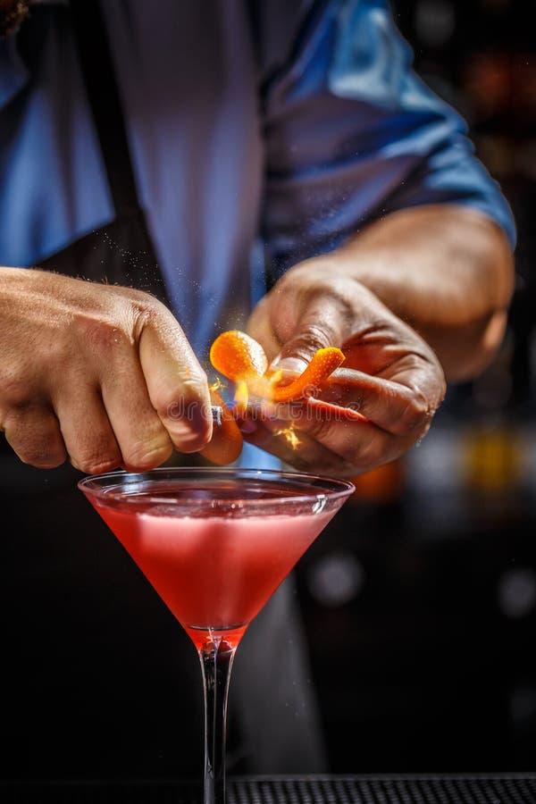 Bartendern dekorerar den kosmopolitiska coctailen royaltyfri fotografi