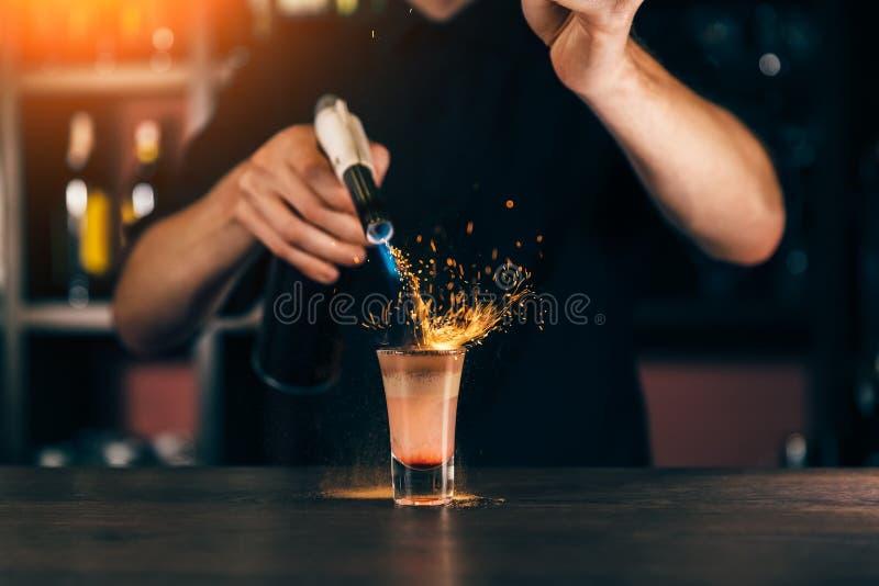 Bartendern gör en coctail av brand Hiroshima coctail Bartendern antänder tändaren på stången arkivbilder