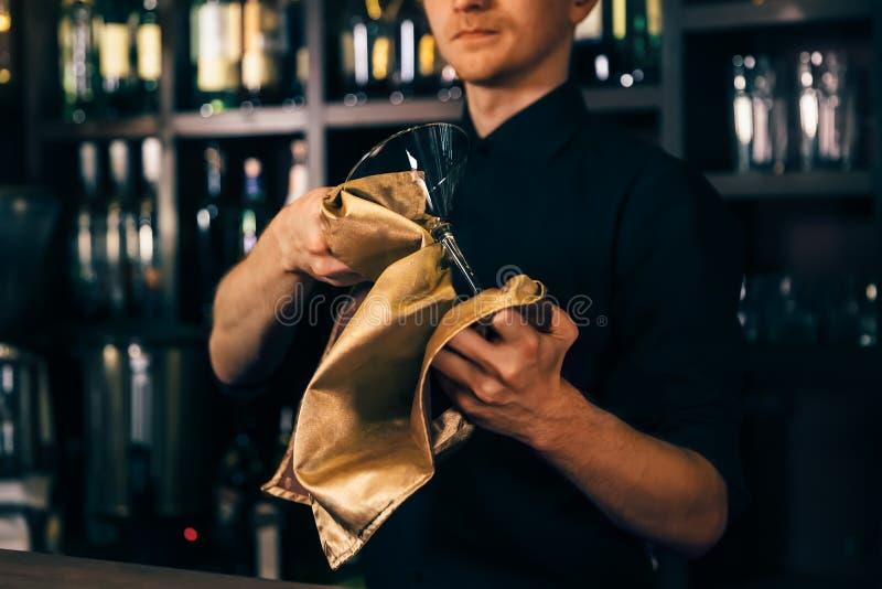 Bartendern gör ren exponeringsglaset med en torkduk på stångräknarebakgrund Bartendern som gör ren exponeringsglaset på stången arkivbild