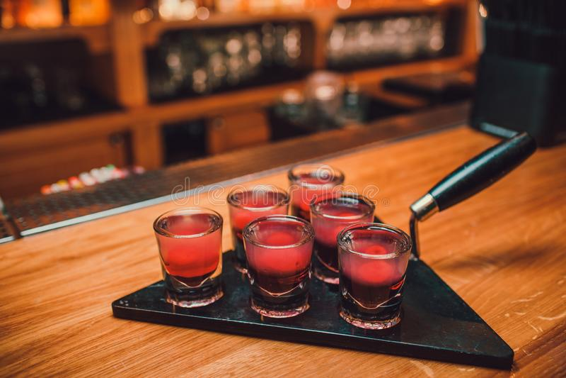 Bartendern häller tequila in i exponeringsglas mot bakgrunden av stången arkivbilder