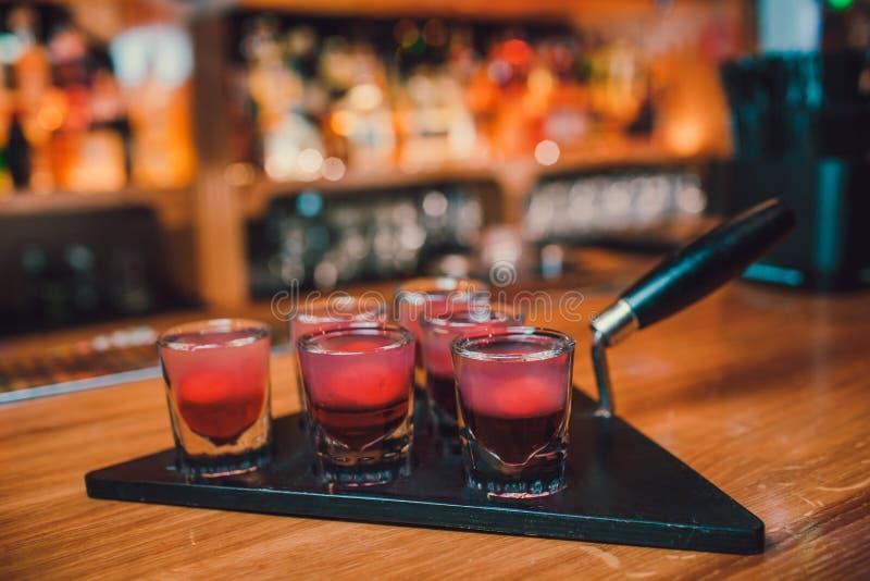 Bartendern häller tequila in i exponeringsglas mot bakgrunden av stången royaltyfria bilder