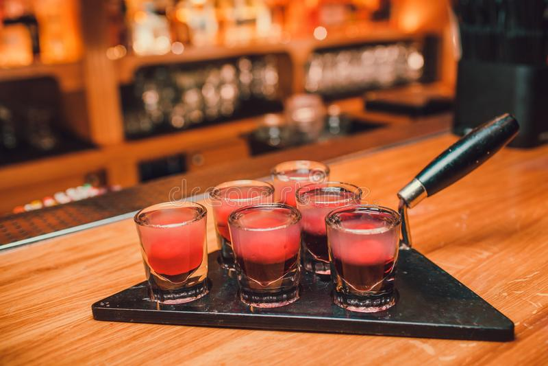 Bartendern häller tequila in i exponeringsglas mot bakgrunden av stången royaltyfri bild