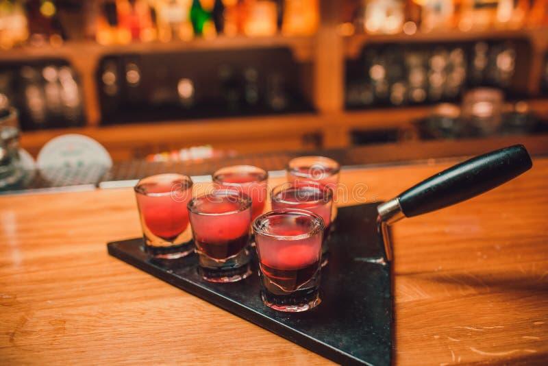 Bartendern häller tequila in i exponeringsglas mot bakgrunden av stången arkivfoton