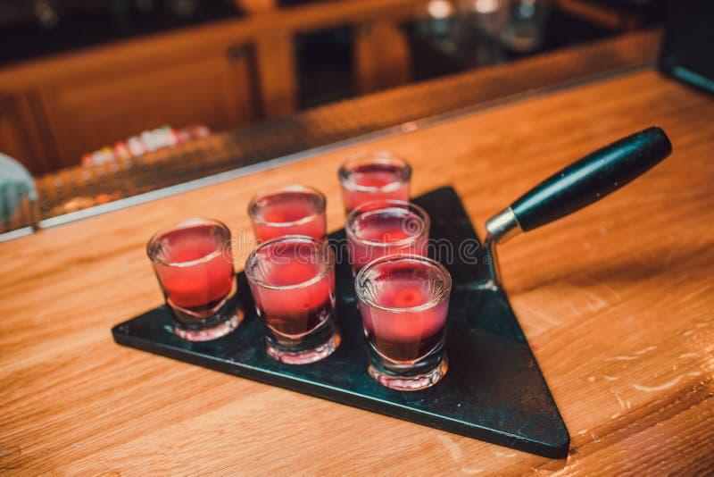 Bartendern häller tequila in i exponeringsglas mot bakgrunden av stången arkivbild
